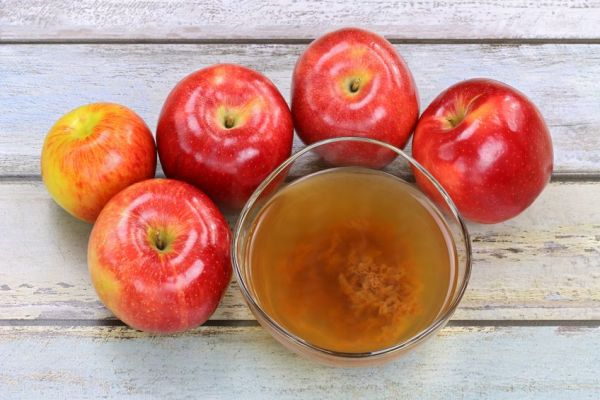 36769077 - fresh apples and a bowl of raw and unfiltered organic apple cider vinegar with mother enzymes