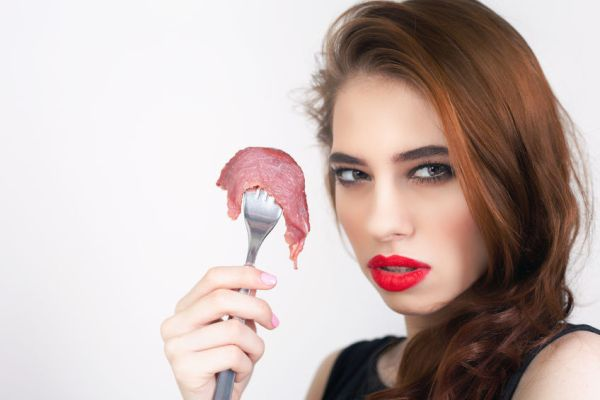55811600 - image of woman holding fork with piece of meat at the restaurant. healthy eating. meat recipes, expiration date, shelf life