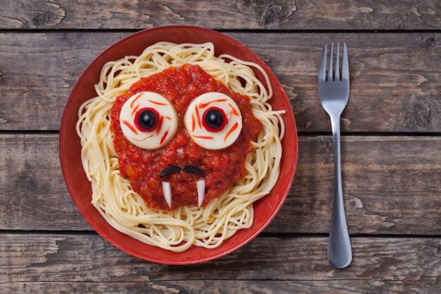 46699378 - halloween scary pasta food vampire face with big eyes and moustaches in red dish for celebration party decoration on vintage wooden table background