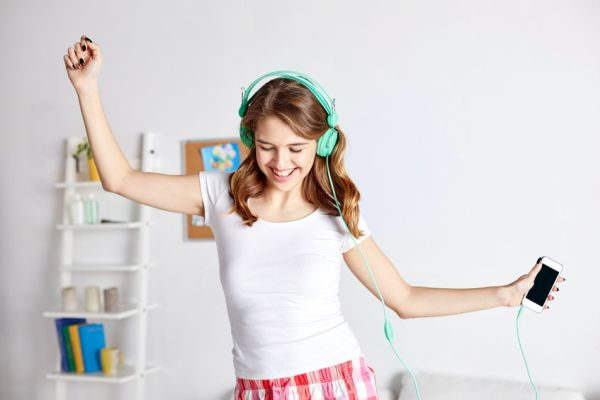 52081559 - people, leisure and technology concept - happy woman or teenage girl in headphones listening to music from smartphone and dancing on bed at home
