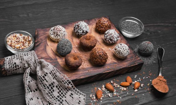 57961500 - sweets handmade chocolates sweet-stuff candies, sprinkled poppy, coconut, linseed, sesame, cocoa, almonds oerhi on a cutting board with lace on a light wooden background in rustic style