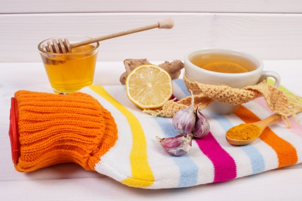 63896627 - hot water bottle, cup of tea with lemon and ingredients for preparation warming beverage for flu and cold, health care concept