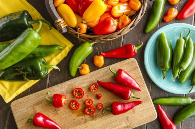 40036748 - assorted colorful varieties of hot and sweet peppers sitting on table with cutting board, yellowe napkin and blue plate