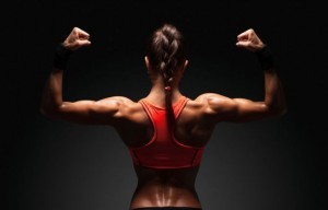 34766325 - athletic young woman showing muscles of the back and hands on a isolated black background with clipping path