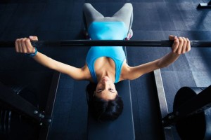38584430 - young fit woman working out with barbell on bench in the gym. bar bench pres