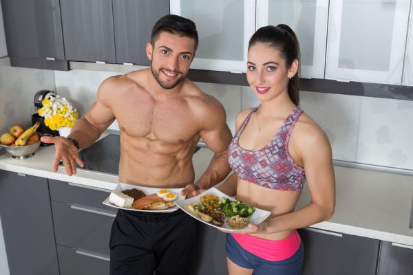 57805380 - fit couple in the kitchen; animal versus plant proteins: one plate with beef, eggs, salmon, cheese and chicken grill and another with nuts, mushrooms, broccoli, lentil, hummus and quinoa