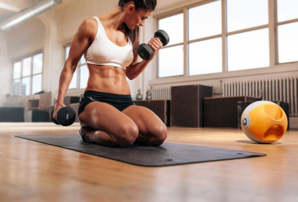 44433995 - physically fit woman at the gym lifting dumbbells to strengthen her arms and biceps. muscular woman sitting on exercise mat looking at her arms.