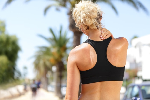 39027577 - neck pain during training. athlete running caucasian blond woman runner with sport injury in sports bra rubbing and touching upper back muscles outside after exercise workout in summer.