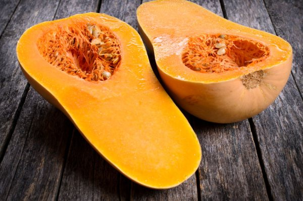 42597325 - butternut squash cut in half on a wooden surface