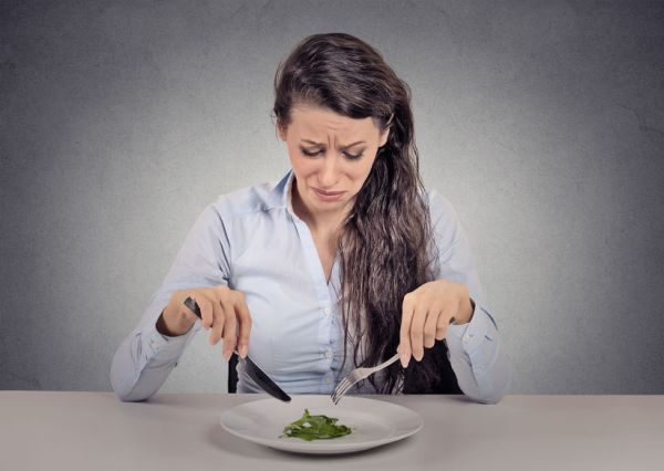 40353346 - young woman tired of diet restrictions eating green salad sitting at table isolated grey wall background. human face expression emotion. nutrition concept