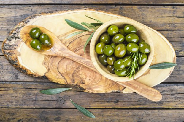 37114421 - wooden spoon and bowl with green olives on a cutting board on the table of the kitchen