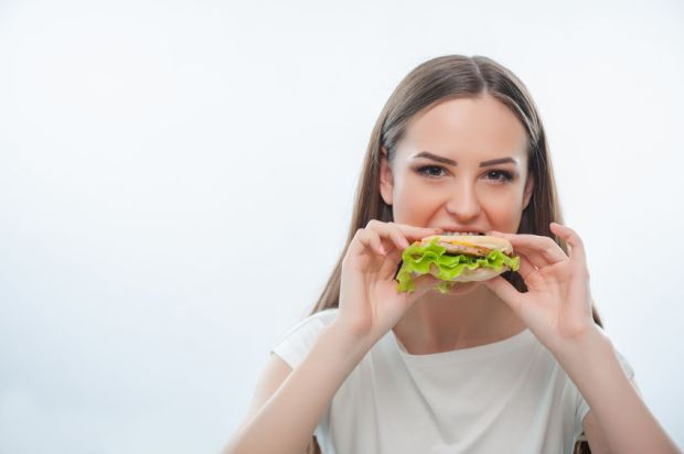 40890989 - hungry pretty woman is biting hamburger gradually. isolated on a white background