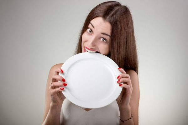 35688727 - young woman bites empty plate. hungry woman with plate in studio on white background