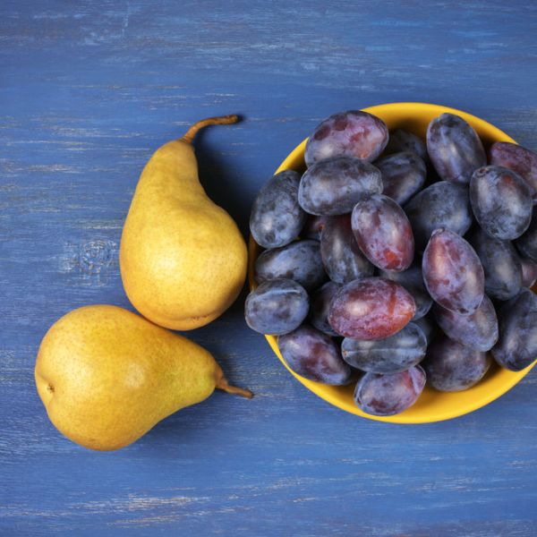 56407467 - heap of fresh blue plums in bowl and two yellow pears on blue painted rustic wood. top view point.