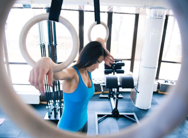 38584036 - tired woman working out on gimnastick rings at gym