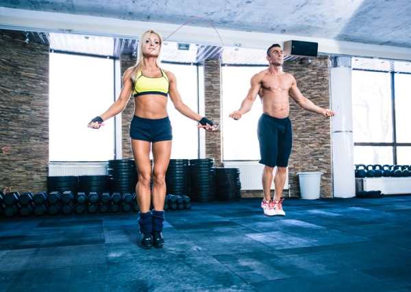38871328 - muscular man and beautiful sporty woman workout with jumping rope in crossfit gym