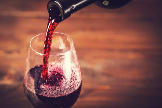 51975832 - pouring red wine into the glass against wooden background