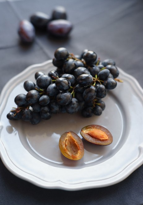 48130773 - black grapes and plums with a stone on the gray plate
