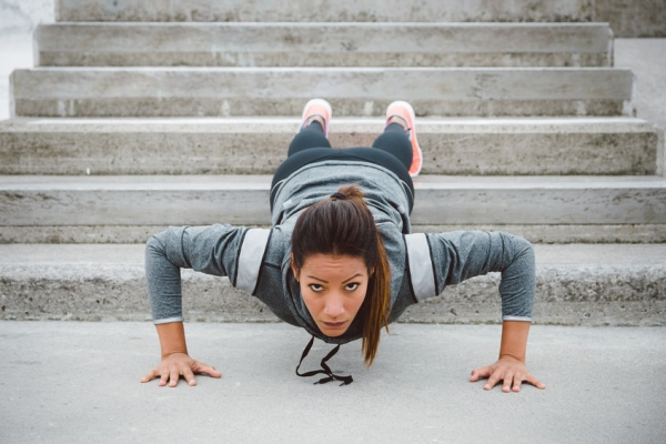 48966608 - urban fitness woman workout doing feet elevated push ups on urban park stairs. motivated female athlete training hard.