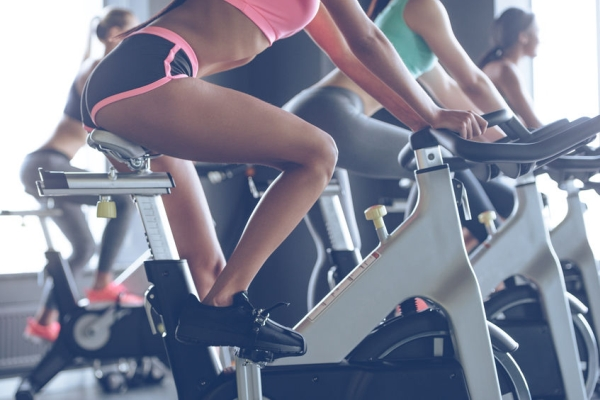 55863296 - power and motivation. side view part of young women with perfect bodies in sportswear looking at camera with smile while cycling at gym