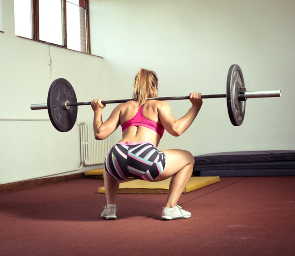 61936281 - young adult girl doing heavy duty  squats in gym with barbell