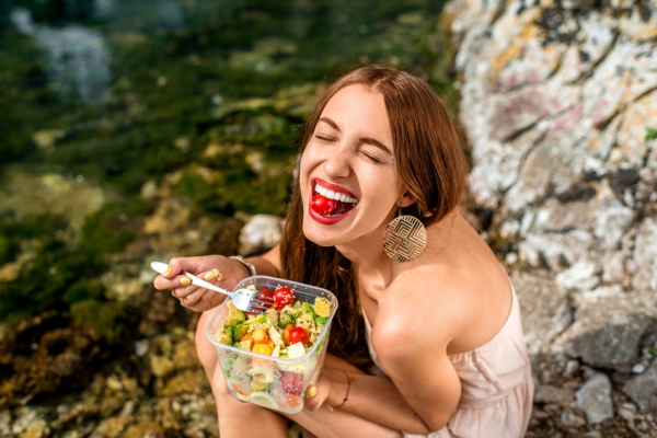 43082756 - woman eating healthy salad from plastic container near the river