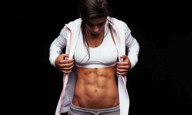 43852700 - portrait of young woman looking at her muscular abs. fitness model on black background