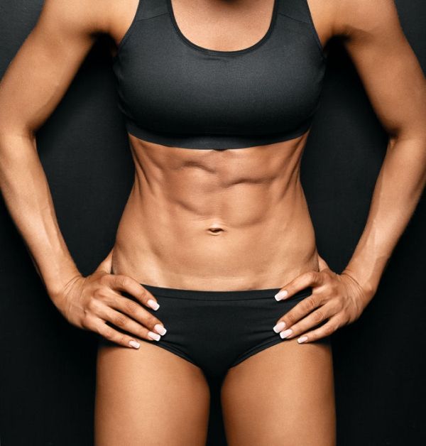 43366581 - beautiful athletic woman shakes her abdominal muscles on dark background