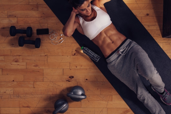 44148586 - sporty young woman lying on exercise mat doing sit-ups. top view of muscular woman doing abs crunches in gym.