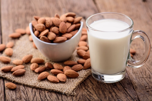 50307518 - almond milk in glass with almonds