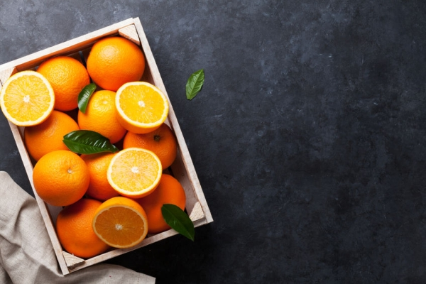 57891048 - fresh orange fruits in wooden box on stone table. top view with copy space