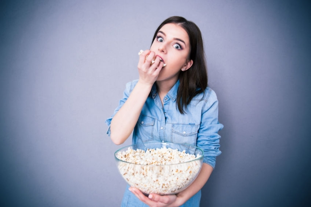 38431011 - young cute woman eating popcorn over gray background. looking at camera