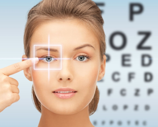 34710495 - medicine, eyesight control, laser correction, people and health concept - beautiful young woman pointing finger to her eye and over blue background with eye chart