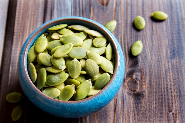 44490866 - pumpkin seeds in blue bowl over wooden background close up
