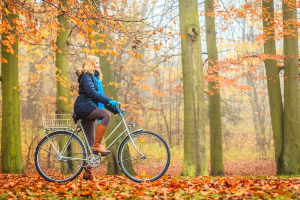 45381230 - happy active woman riding bike bicycle in fall autumn park. glad young girl in jacket and scarf relaxing. healthy lifestyle and recreation leisure activity.