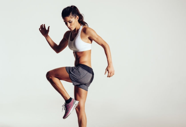 35753749 - attractive fit woman exercising in studio with copyspace. image of healthy young female athlete doing fitness workout against grey background.