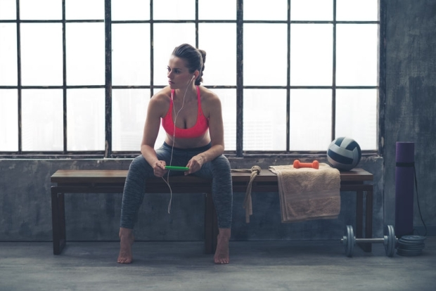 43792727 - an athletic woman watches something in the distance. she is sitting on a bench by a window in a loft gym, holding her device and listening to music.