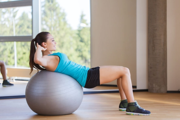38675555 - fitness, sport, training and people concept - smiling woman flexing abdominal muscles with exercise ball in gym
