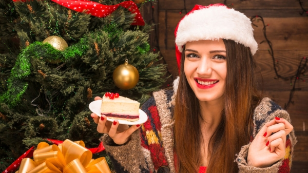 47840698 - new year and christmas concepts. pretty lady in santa hat eating a delicious piece of cake while sitting near new year tree.
