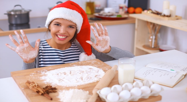 47489651 - christmas baking santa woman smiling happy having fun with christmas preparations wearing santa hat