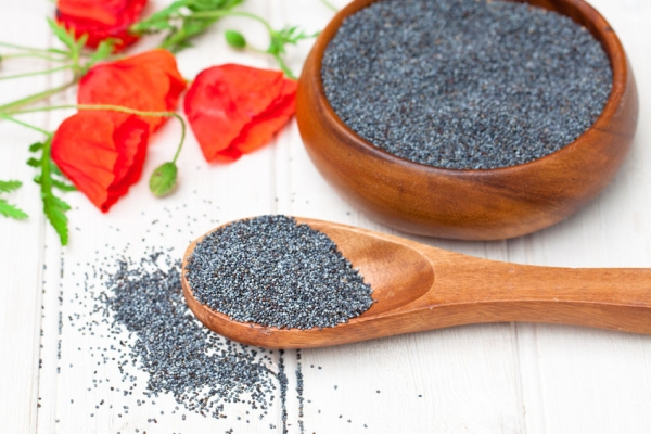55447433 - poppy  seeds in a wooden bowl on a table with spoon