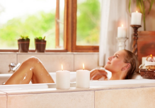 46090018 - soft focus photo of gentle young woman lying down in bath tub with foam and candle, enjoying spa procedure in the luxury resort