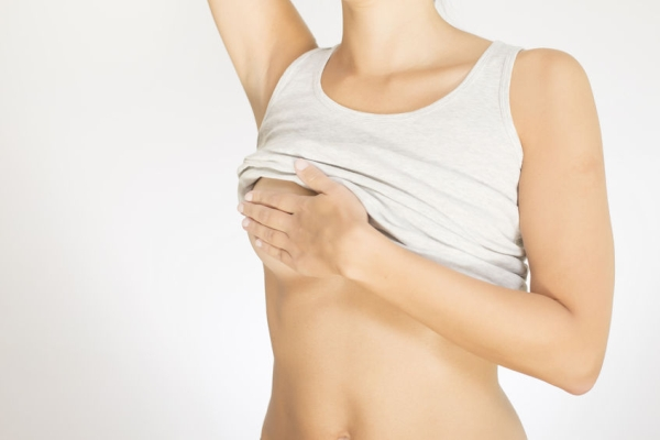 22553153 - close up view of the female torso with a grey shirt testing her breast for cancer flattening the tissue with one hand and manipulating to detect lumps with the fingers on her other hand