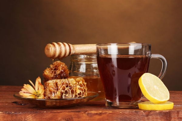 12439013 - honey, lemon, honeycomb and a cup of tea on wooden table on brown background