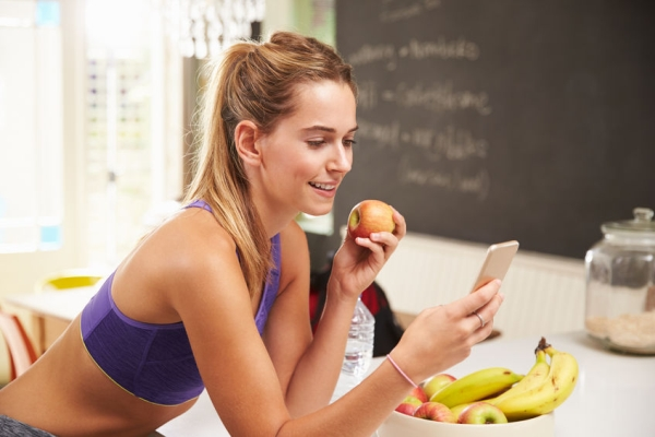 41142953 - woman wearing gym clothing looking at mobile phone