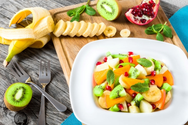 56360043 - fruit salad in a wide rim square plate, close-up, top-view