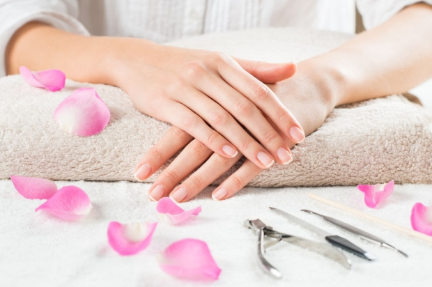 41263300 - closeup shot of female hands with french manicure on a towel surrounded by petals and manicure set. woman getting nail manicure. shallow depth of field with focus on woman hand.