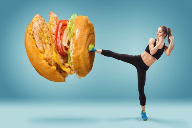 55035296 - fit, young, energetic woman boxing unhealthy food on blue background. concept of diet and healthy lifestile
