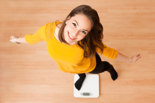 52892372 - portrait of young brunette beauty using household scale.