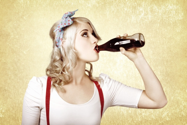 48589623 - beautiful blond pinup girl drinking soda drink at vintage sweets shop